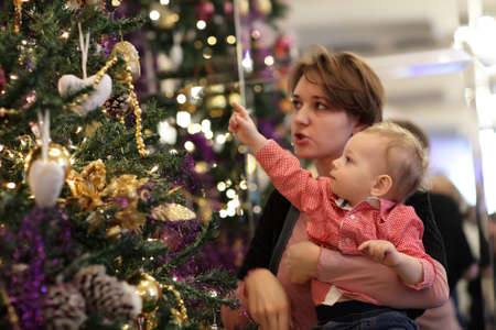 Mother and her baby with Christmas tree at home photo