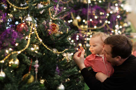 Baby is touching decoration of Christmas tree at home photo