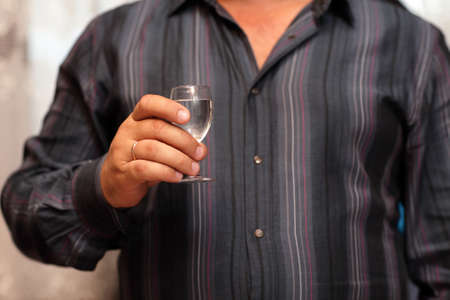 Man is holding glass of vodka at a restaurant photo