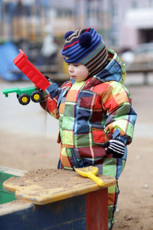 Toddler is playing with toy car at outdoor playground photo