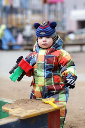 Toddler is with toy car near sandbox at playground photo