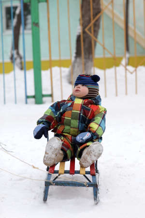Toddler is sitting on a sled in winter photo