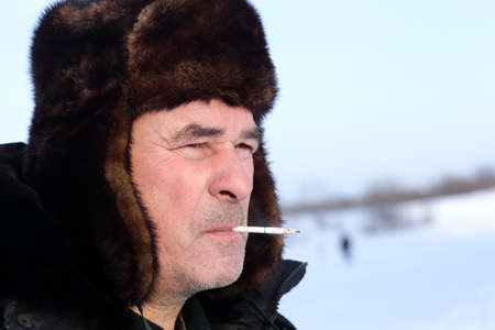 Senior man is smoking sigarete outdoor in winter photo