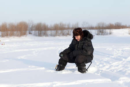 Winter fisherman sitting with fishing rod, Tyumen region, Russia photo