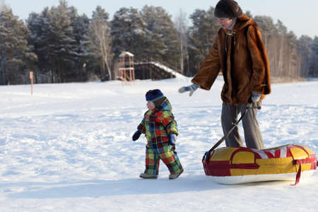 Mother and toddler are walking on a snow, Siberia, Russia photo