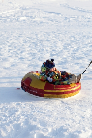 Toddler on a sled in winter, Siberia, Russia photo