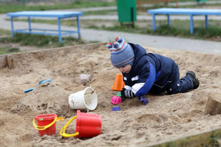 Toddler is playing in a sandbox in autumn photo