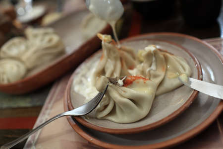 Khinkali with pepper and sour cream  It is a dumpling which originated in the Georgia Stock Photo - 17953553