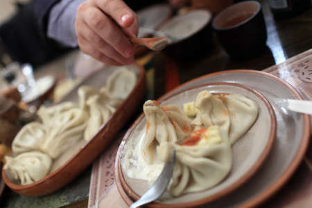 Person sprinkles with pepper Khinkali  It is a dumpling which originated in the Georgia Stock Photo - 17972341