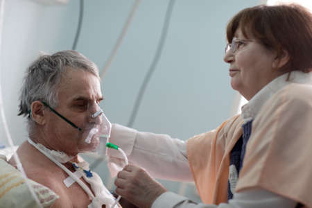 Doctor is setting oxygen mask on a patient photo