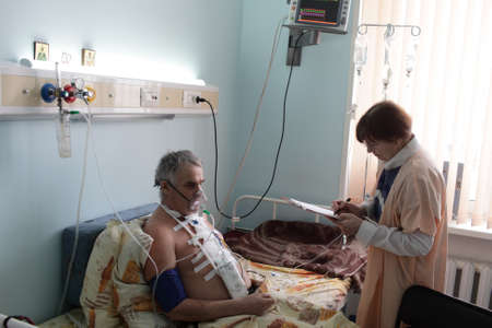 russian man: Doctor is writing prescription for a patient in a hospital ward Stock Photo