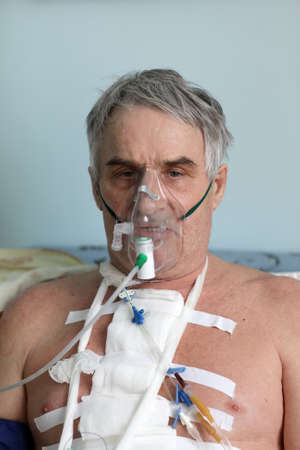 Man with oxygen mask in a hospital ward photo