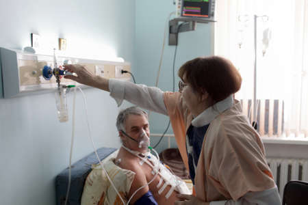 Nurse is adjusting the level of oxygen for a patient