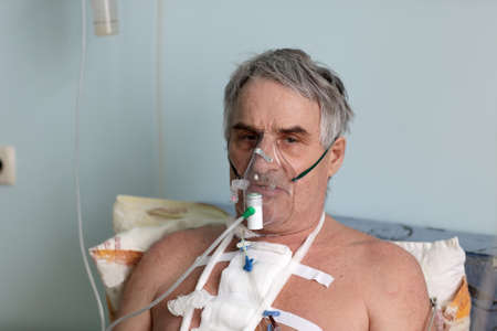 Person with oxygen mask in a hospital ward photo