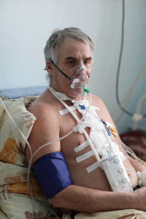 Senior man with oxygen mask in a hospital ward photo