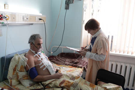 Doctor is writing medical history of a patient in a hospital ward photo