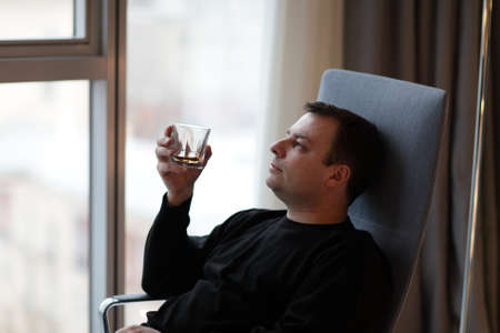 Man holds glass of whiskey in a hotel room photo