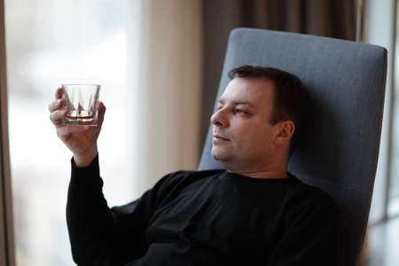 The man with whiskey is in a hotel room photo