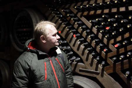 Man is looking on bottles of wine in cellar  photo