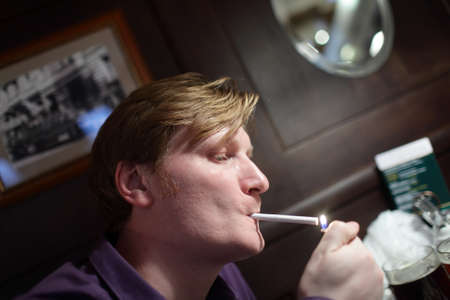 Man lights a cigarette in a pub photo
