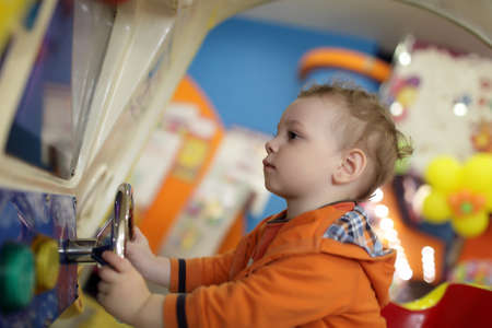 The child and amusement car at indoor playground photo