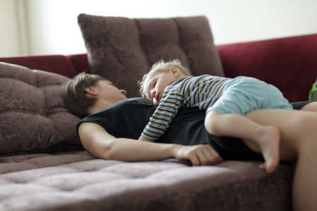 Sleeping mother and boy on a sofa at home photo