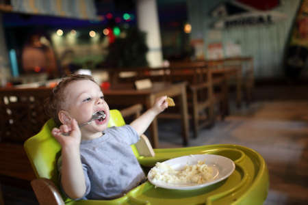Boy has a lunch in a high chair at a restaurant Stock Photo