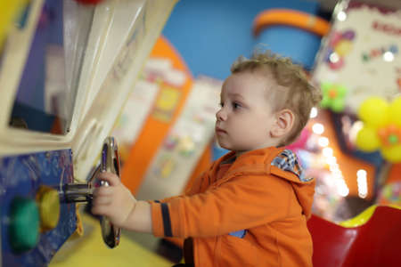 Child is playing with amusement machine at indoor playground photo