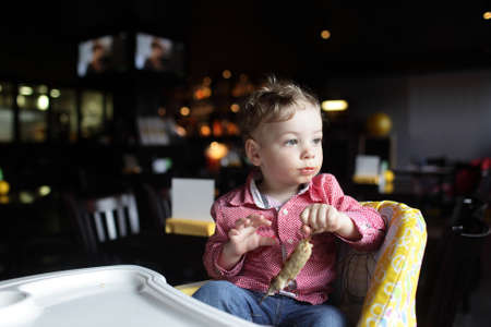 highchair: Child with kebab in a high chair at a restaurant