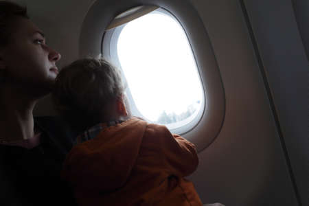 Family is looking through window at airplane