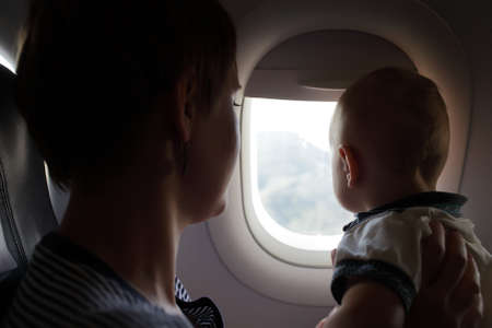 Mother with son are looking through window on the flight
