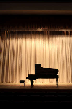 Concert grand piano at theatre stage with brown curtain photo