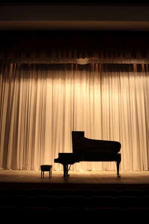 piano: Concierto de piano de cola en el escenario del teatro con la cortina marr�n