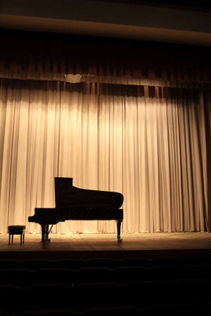 The grand piano on the brown curtain background photo