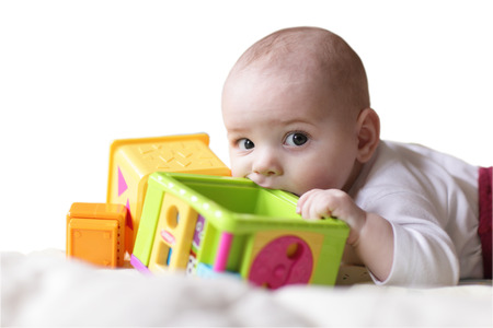 Baby bites toy block on a white background