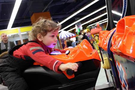Child driving motorbike toy at an amusement park