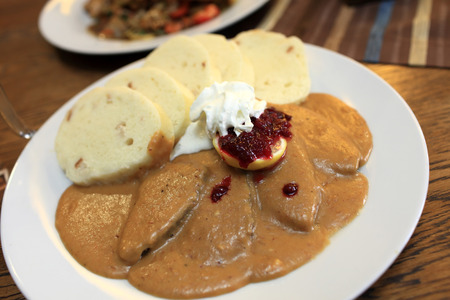 Goulash served with czech bread dumplings on a white plate