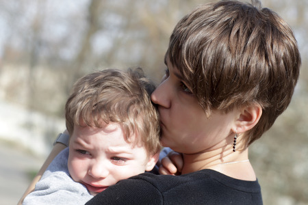 Mother kissing her crying son in the park photo