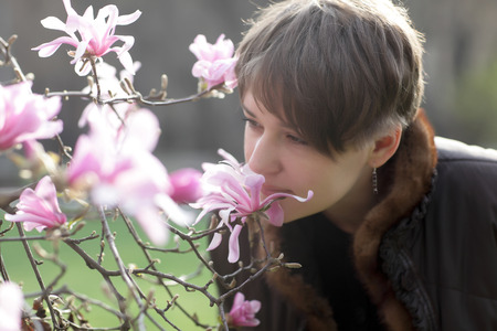 Woman smelling a flower in the spring park photo