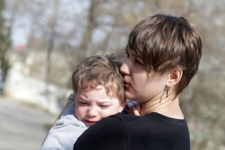 Mother hugging her crying son in the park photo