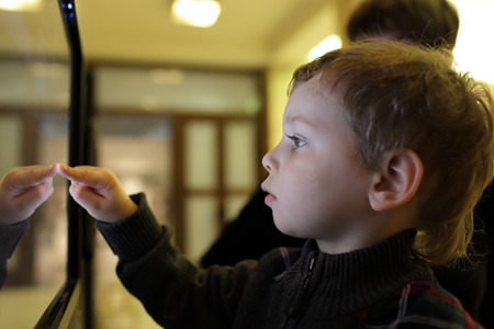 Boy using interactive touch screen in a museum
