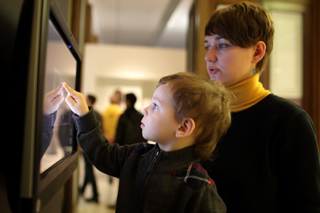 Family playing with touch screen in a museum photo