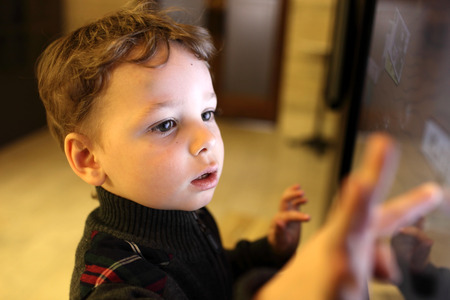 niño empujando: Cabrito usando la pantalla táctil interactiva en un museo