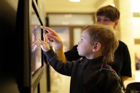博物館でタッチ スクリーンを使用して彼女の息子を持つ母