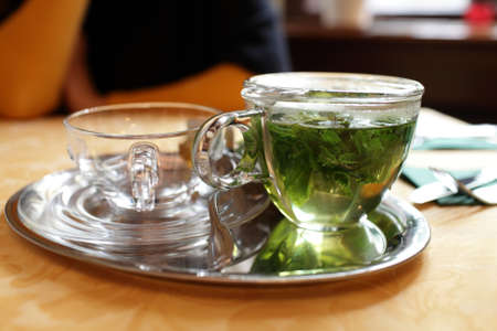 Glass teapot with mint tea in the cafe photo