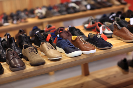 Shoes on the wooden shelf in the store Standard-Bild