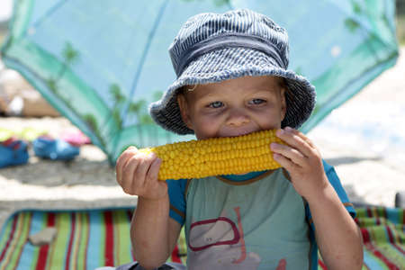 Boy in panama eating corn on picnic