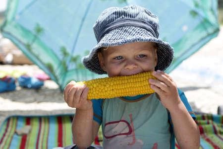 Jongen in Panama, die maïs op picknick eet