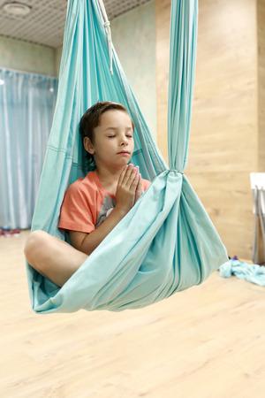 Boy practices aerial yoga in a gym Reklamní fotografie