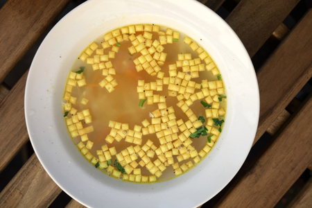 Chicken bouillon with soup mandels on table Stockfoto